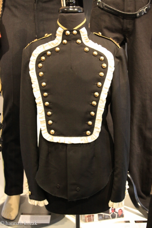 A black wool long-sleeve shirt with snap front closure and lined in black silk. The bib front, western style shirt is embellished white silk ruffle at cuffs and bib front, featuring gold tone metal buttons. Collar and epaulets feature gold piping detailing with faux jeweled costume pieces on each epaulet. The jacket was made by Western Costume Co. Michael Jackson was photographed wearing this shirt with his longtime manager, Frank Dileo, in the early 1980s.
